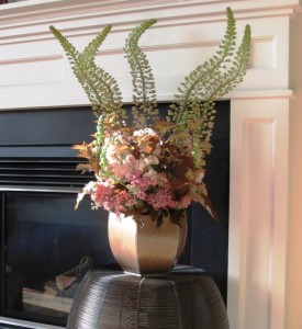 The copper container highlights the rich colors of the foliage and flowers.